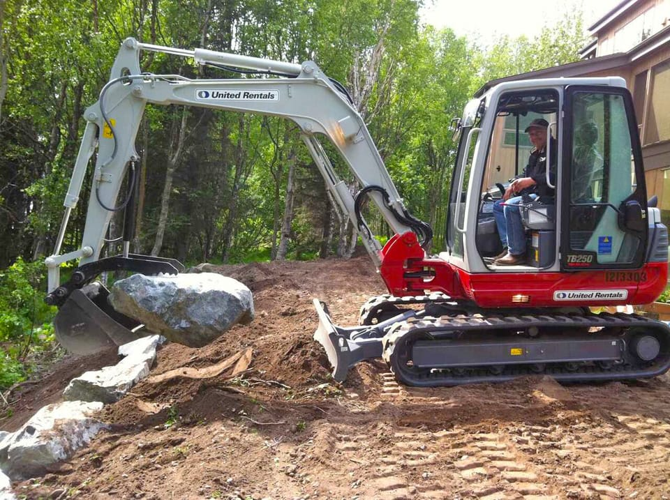 Tractor placing another boulder in retaining wall